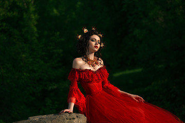 Young Countess in a luxurious red dress sitting of nature.
