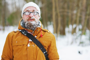 Portrait of a bearded man with glasses, and plastered with snowflakes and snow on the face.