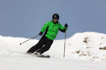 Male skier skiing on ski slope