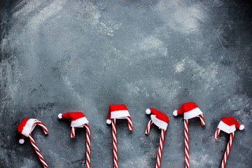 Christmas background with candy cane in santa hat