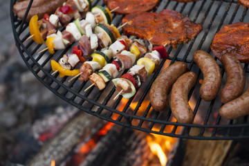 Sausage, meat and colorfull shashliks with peper and courgette on grill barbecue under fire flames.