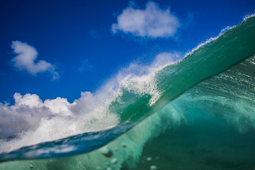 Green Shorebreak wave split view with underwater part and cloudy blue sky