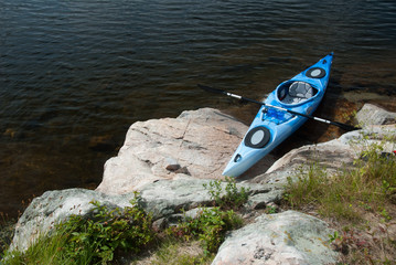 Blue kayak on rock shore