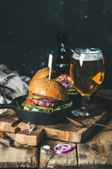 Homemade beef burger with crispy bacon and vegetables in small pan and glass of wheat beer on rustic serving board over shabby wooden background, dark blue plywood wall, selective focus, copy space