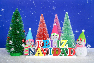 Feliz Navidad, Merry Christmas in Spanish colorful wood sign, red, pink, green pine trees with snowman on faux snow blue background white dots and stars.