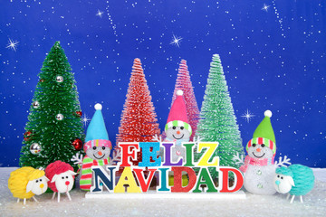 Feliz Navidad, Merry Christmas in Spanish colorful wood sign, red, pink, green pine trees with snowman and colorful yarn sheep on faux snow blue background white dots and stars.