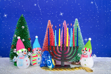 Menorah and  red, pink, green pine trees with snowman on faux snow blue background white dots and stars. Christmas and Hanukkah together. Multi faith celebration.