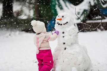 A toddler girl in a pink snowsuit with wooly hat toque builds a large snowman with carrot nose and smiling face in backyard with snowflakes snow falling in winter at Christmas