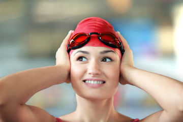 Beautiful girl wearing goggles in swimming pool, closeup