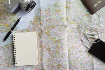 Vintage camera, notebook ball pen and passport on Europe map, Holidays travelling concept.