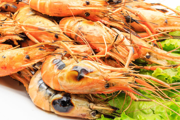 Charcoal grilled river prawns or shrimp serve with fresh Lettuce on white plate over white background, Thai style food