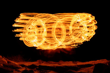 Light painting with fire sticks - effect created by slow shutter speed