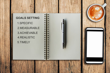 Goal setting as memo on notebook and coffee cup with mobile phon