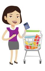 Female customer counting on calculator.