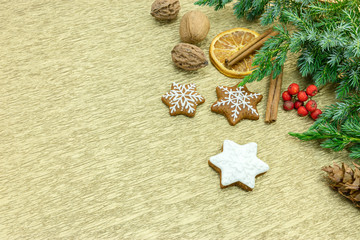 homemade gingerbread cookies with fir tree branches, spice and red berries on gold wrapping paper