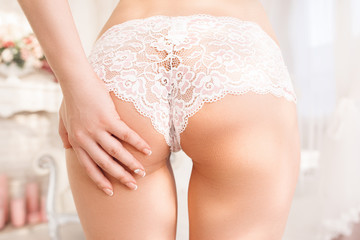 Nude woman touching her perfect buttocks. Close-up of perfect butt in white lace panties with hand stroking it. Sex, seduction, temptation, antiage concept