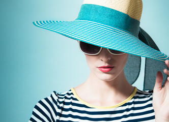 Portrait of female fashion model wearing blue hat.