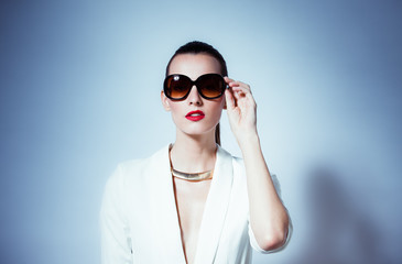 High fashion portrait of girl wearing sunglasses in a studio setting.