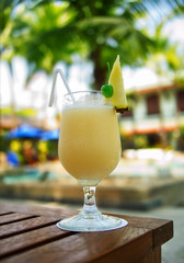 Yellow Pina Colada cocktail on a table on tropical island. Palm