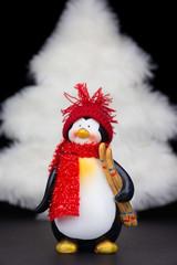Penguin figurine with white christmas tree on black