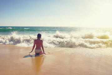 Topless woman sitting in surf on beautiful beach at Albufeira, Portugal at sunset. travel concept