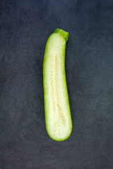 Two halves of fresh green zucchini isolated on dark gray slate s