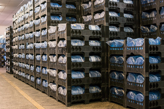 Many crates with bottles. Interior of storehouse. High quality mineral water. Each jug holds five gallons.