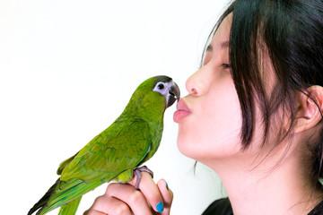 Green macaw bird pet kiss to woman.