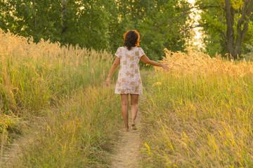 Adult brunette woman  in a dress walking on a meadow path