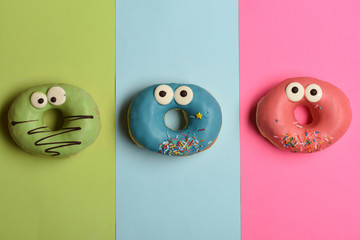 Funny glazed donuts on colorful background