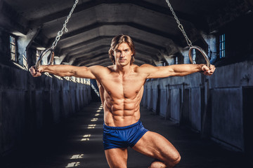 Athletic muscular male posing with gymnastic rings in a dark tunnel