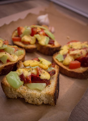 Bruschetta sandwitches with  garlic, cheese, tomatoes and peppers on a brown paper and wood.