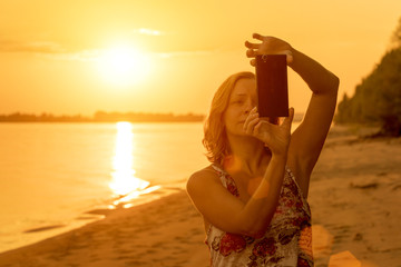 Woman blonde in dress makes selfie for cellphone on a sandy beach at sunset