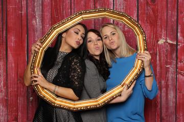 Drei Frauen schauen durch einen Bilderrahmen und machen einen Kussmund - 3 Mädchen mit Kussmund schauen durch einen goldenen Rahmen