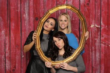 3 Mädchen schauen durch einen Bilderrahmen - Photobooth