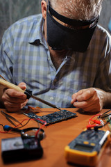 Senior electrician with soldering iron