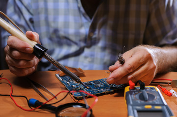 Closeup of male hands soldering computer board.