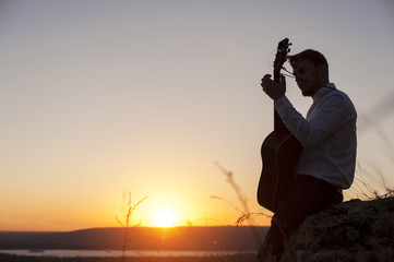 Silhouette of young guitarist playing outdoors