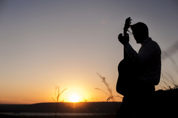 Silhouette of male guitarist playing outdoors