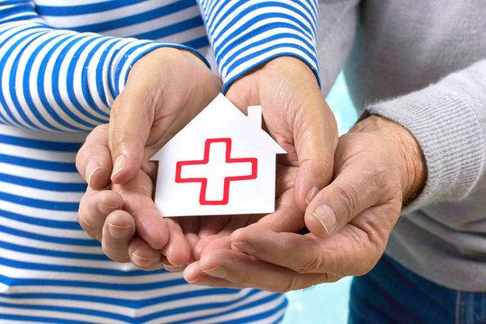 Hände halten ein Haus mit roten Kreuz
