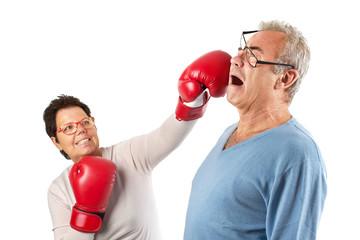 Senioren - Frau boxt Mann mit roten Boxhandschuhen, isoliert