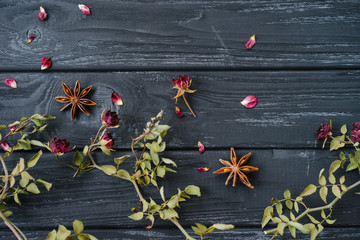 Autumn or winter composition of dried flowers and spices on wooden background. Top view, flat lay, copy space.
