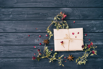 Autumn or winter composition of dried flowers, spices and wrapped gift on wooden background. Top view, flat lay, copy space.