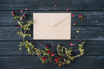Autumn or winter composition of dried flowers and craft envelope on wooden background. Top view, flat lay, copy space.