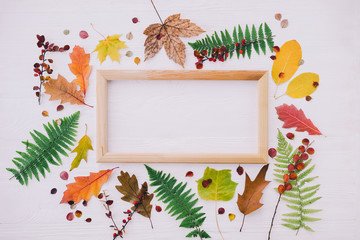 Composition with autumn leaves and picture frame on white wooden background. Flat lay, copy space.