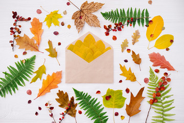 Autumn composition of colorful leaves and craft envelope on white wooden background. Top view, flat lay, copy space. Thanksgiving day concept.