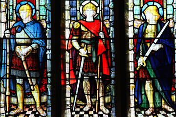 Medieval knight saints on a stained glass window at St Peter's Church Carmathen, Wales, UK