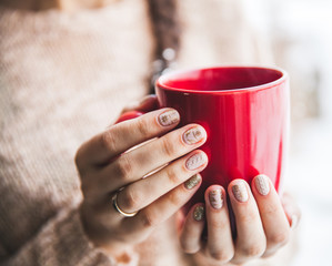 Woman's hand holding a red cup of coffee. With a beautiful winte