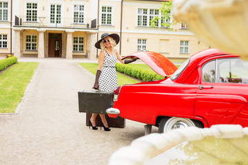 Woman holding vintage suitecase next to red retro car