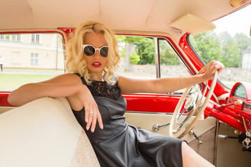 Glamorous woman driving a vintage car